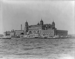 a black and white photograph of Ellis Island's brick facade with several barges in front